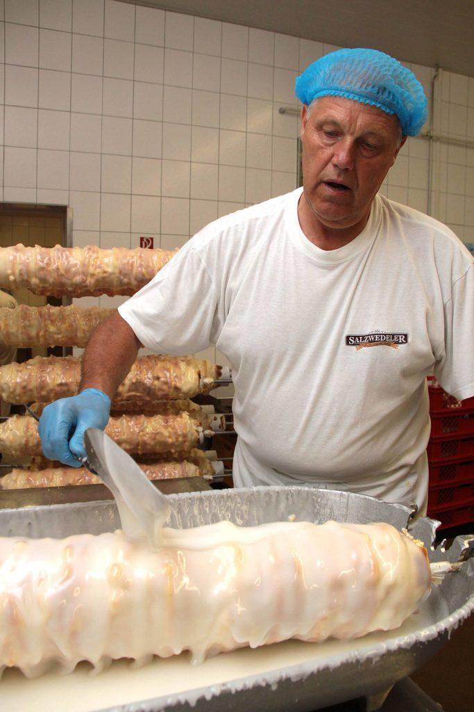 Der Baumkuchen erhält seine weiße Zuckerglasur