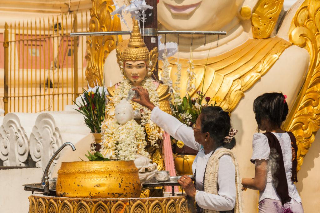 Gläubige übergießen den Buddha ihres Geburtstags-Wochentages mit Wasser