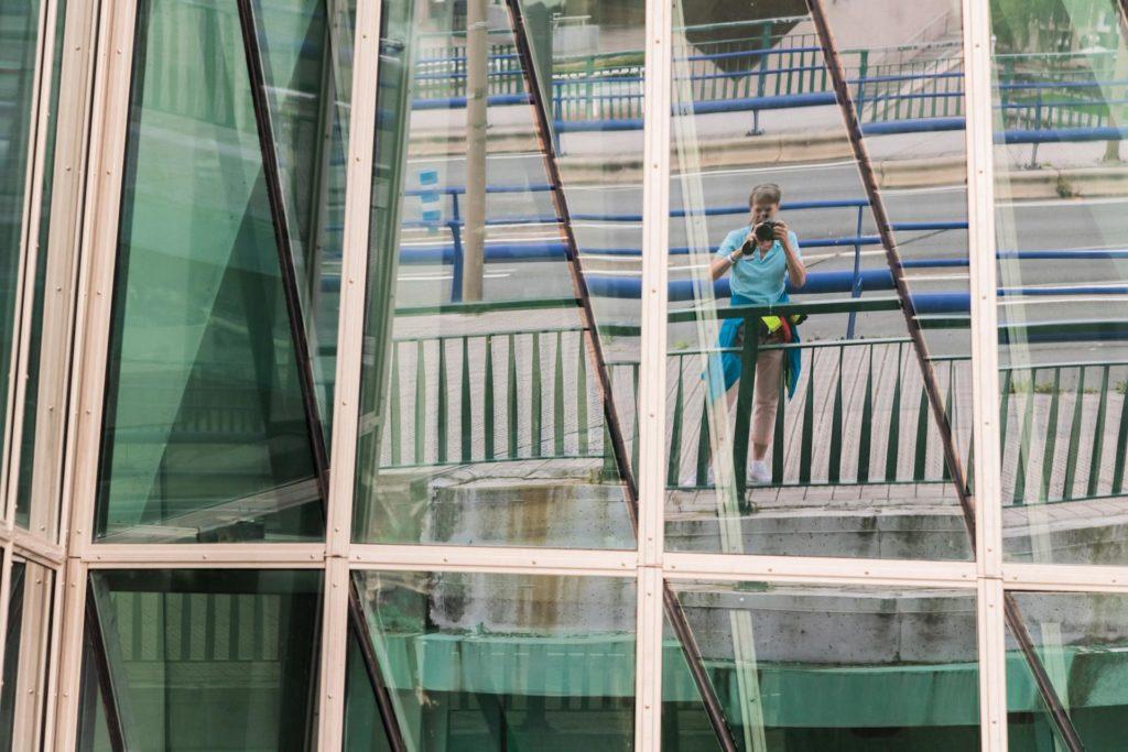 Die Autorin Marieluise Erhart spiegelt sich in der Glasfassade des Museums